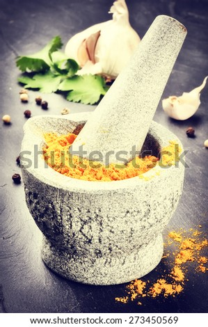Setting with curry powder in rustic stone mortar - stock photo