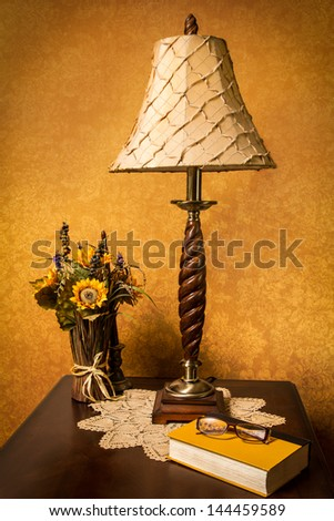 Setting with lamp, book and flowers against gold textured wall - stock photo