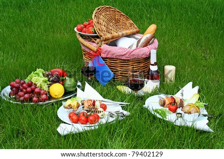 Setting with picnic basket and different food on grass - stock photo
