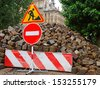 Setts heap and appropriate traffic signs at street repair site in old city (Lviv, Ukraine) - stock photo