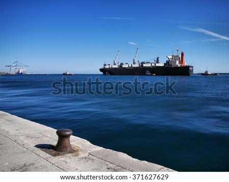 Setubal, Portugal, 8th September 2013, Cargo Ship underway with tugs assistance to quayside. - stock photo