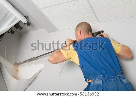 Setup man drills wall rock drill. Work on installing a new air conditioner. - stock photo