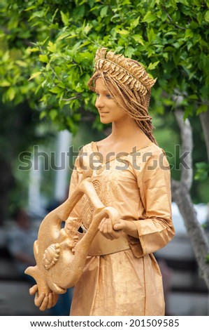 SEVASTOPOL, RUSSIA - JUNE 13:  Mime artist performs as living statue for tourists Sevastopol 2014. Golden lady with lyre in greek style. - stock photo