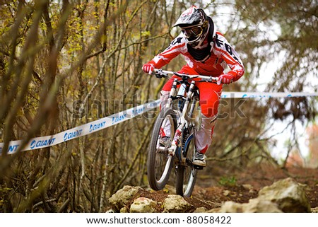 "SEVASTOPOL, UKRAINE - NOVEMBER 3: Racer Denis Bauzin competes in the mountain bike event ""Listopad Bike Session 2011"" on November 3, 2011 in Sevastopol, Ukraine - stock photo"