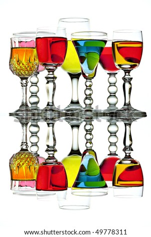 Seven beautiful wine glasses with colorful beverages and reflections - stock photo