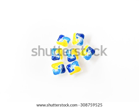 seven  blue and yellow dishwasher tablets on isolated white background with shadow - stock photo