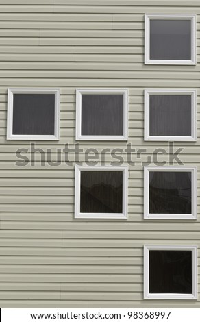 Seven boarded windows with identical white frames on beach house
