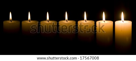 Seven candles burning in the dark - stock photo
