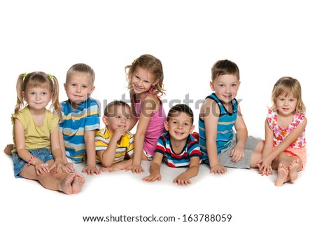 Seven children are lying and sitting on the floor on a white background