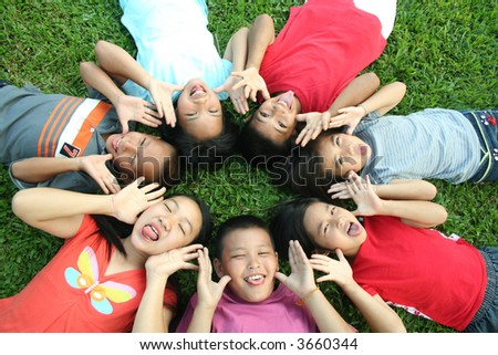 Seven children playing in the park. - stock photo