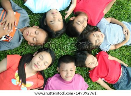 Seven children sleeping in the park.  - stock photo