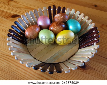 Seven color easter eggs in decorative wooden basket - stock photo