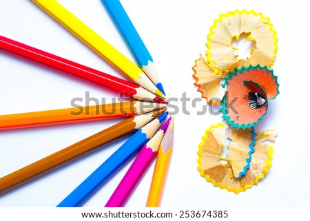 seven colored pencils and shavings on white background with copy space - stock photo