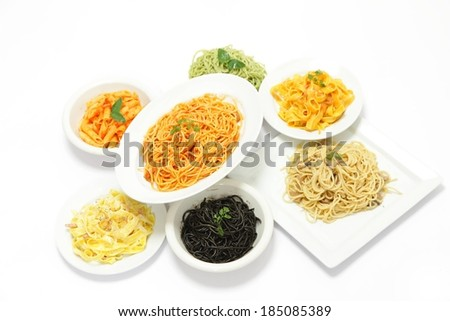 Seven different dishes filled with various types of pasta. - stock photo