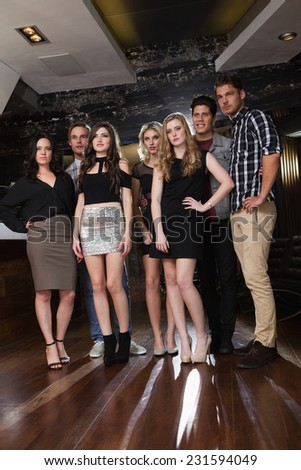 Seven focused friends standing and posing together at the nightclub - stock photo