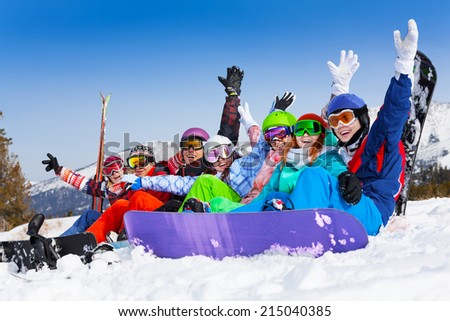 Seven happy smiling friends wearing ski mask sitting together lifting hands up in the air on the mountains background - stock photo