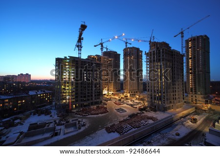 Seven high buildings under construction with cranes at evening - stock photo