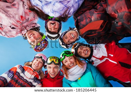 Seven laughing friends in circle wearing goggles