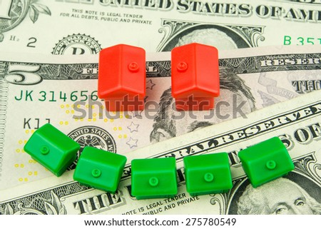 Seven little green and red houses made of plastic are laying on one dollar banknote forming a smile - stock photo