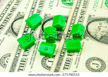 Seven little green houses made of plastic are laying on one dollar banknote - stock photo