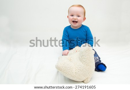 Seven month old white laughing baby boy, with blue eyes and red hair, sitting on a white mattress and plays with his teddy bear. He is wearing a blue bodysuit and blue socks. Isolated on white. - stock photo