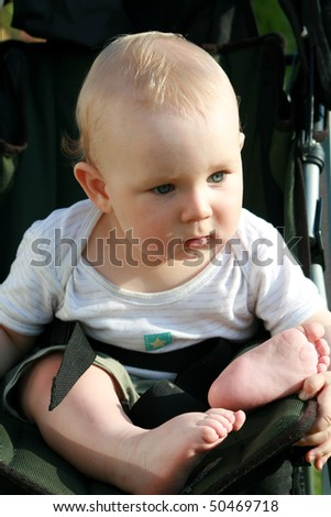 Seven months old baby boy sitting in a baby stroller. - stock photo