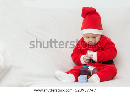 Seven months old baby girl in Santa Claus dress sitting on a white blanket, playing with little gifts