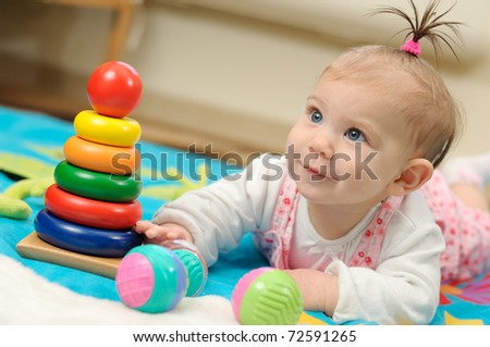 Seven months old  girl witch toy on blanket - stock photo