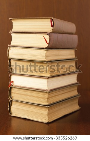Seven of old books stacked on a table - stock photo