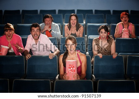 Seven people screaming and scared in a movie theater - stock photo
