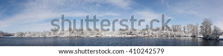 Seven photo panorama of a beautiful snow covered  trees along a lake with a nice blue sky with soft white clouds. - stock photo