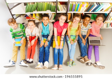 Seven smiling children sitting together on floor - stock photo