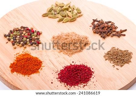 Seven spices (pepper, adjika, Sumy, cardamom, Zira, cinnamon, salt and herbs) on a round cutting board.  - stock photo