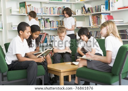 Seven students in library reading books - stock photo