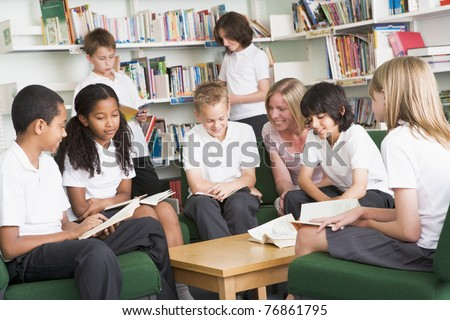 Seven students in library reading books with teacher - stock photo
