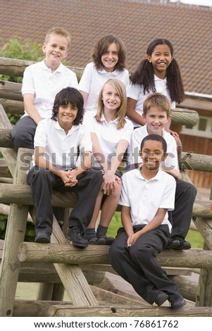 Seven students sitting on wooden structure outdoors - stock photo