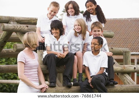 Seven students sitting on wooden structure with teacher standing beside them - stock photo
