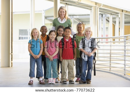 Seven students standing with teacher outdoors at school - stock photo