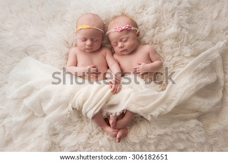 Seven week old fraternal, twin baby girls sleeping on a white flokati rug. - stock photo