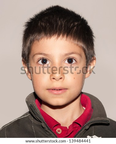 Seven year kid passport photo, against neutral background. - stock photo