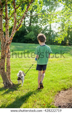 Seven year old boy walking his dog on a sunny day at the park - stock photo