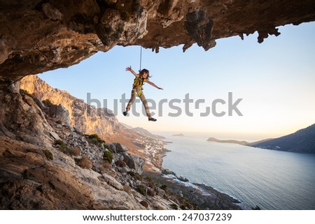Seven-year old girl hanging on rope while lead climbing at sunset