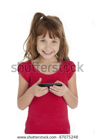 Seven year old girl holding cell phone, smiling at camera, on white background. - stock photo