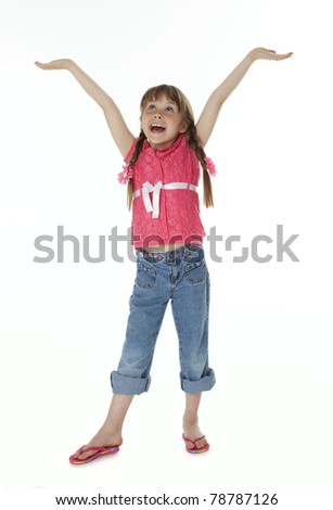 Seven year old girl standing on white background looking upward with arms extended upward.