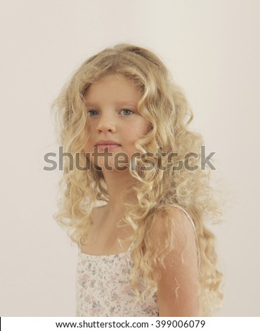 Seven years baby girl with beautiful long blonde curly hair and big blue eyes looking at the camera, white background - stock photo