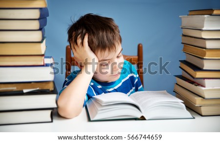 Seven Years Old Child Reading A Book At Home. Boy Studing At Table On Blue