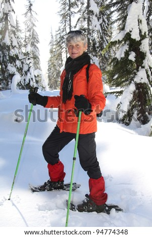 Seventy year old lady having fun snowshoeing on Mount Seymour, Vancouver, Canada. - stock photo