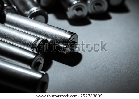 Several AA batteries in perspective closeup view on black background - stock photo