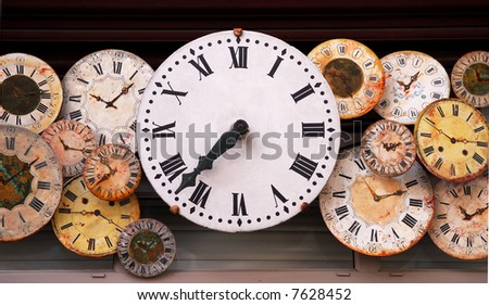 Several antique clock faces of different sizes and styles - stock photo
