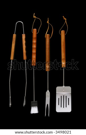 Several barbecue tools and utensils over black - stock photo